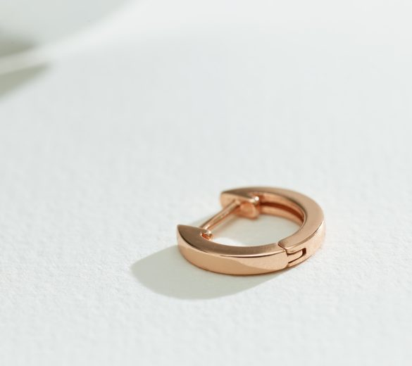gold earring on a white paper background